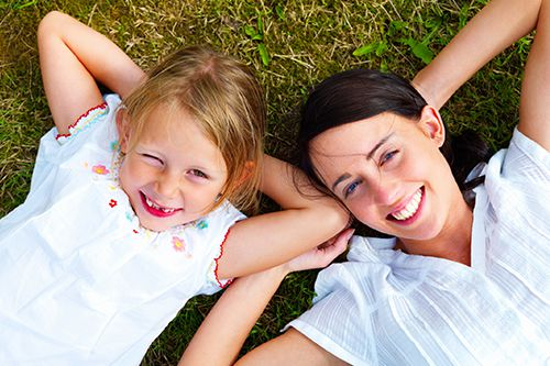 mother and child smiling whilst laying down on the grass