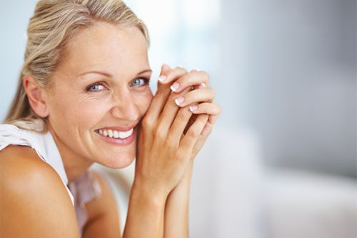 women smiling whilst holding her hands